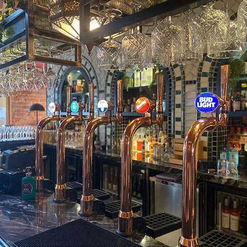 Photograph of the draught beer punps on Rio Jesmonds bar. Copper pipes and illmunated beer brands.