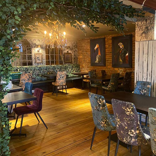 Photo showcasing the fixtures & fitings of Rio Jesmond. Flowered walls, hardwood floors & floral seat covers.