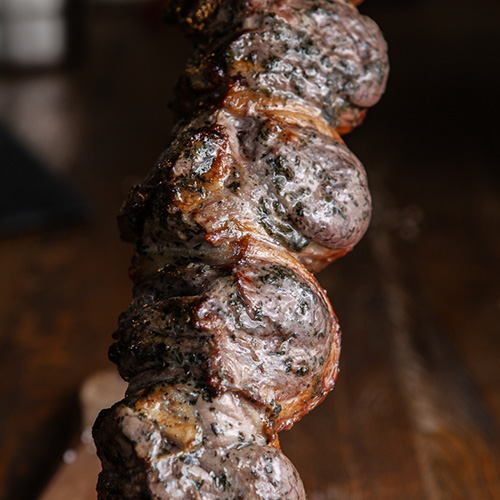 Close up photograph of skewered lamb with mint glazing ready to be carved.