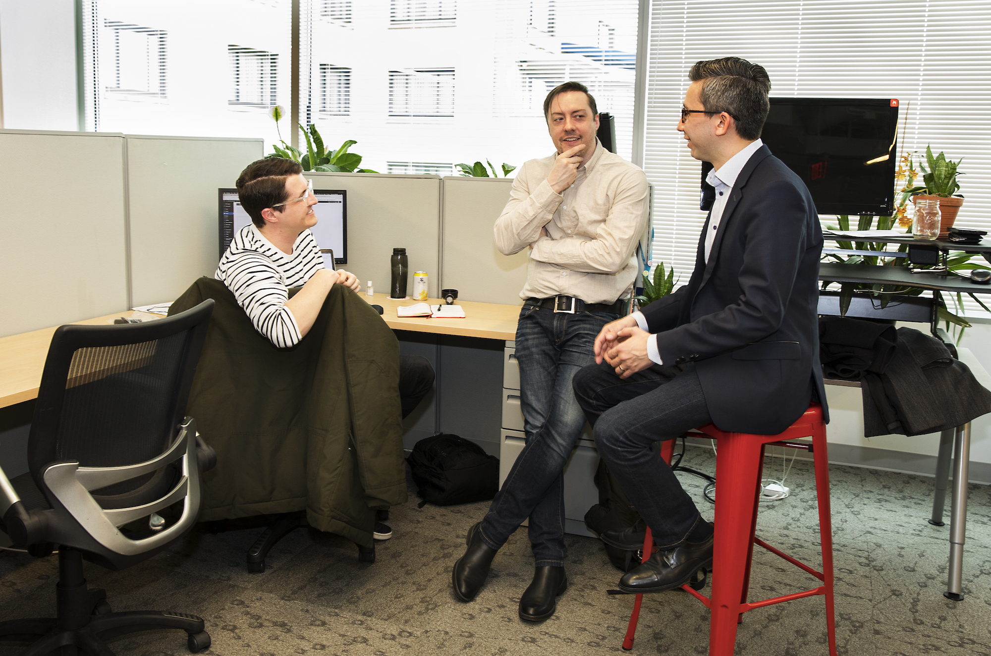 Social Driver CEO, Thomas Sanchez chats with two employees