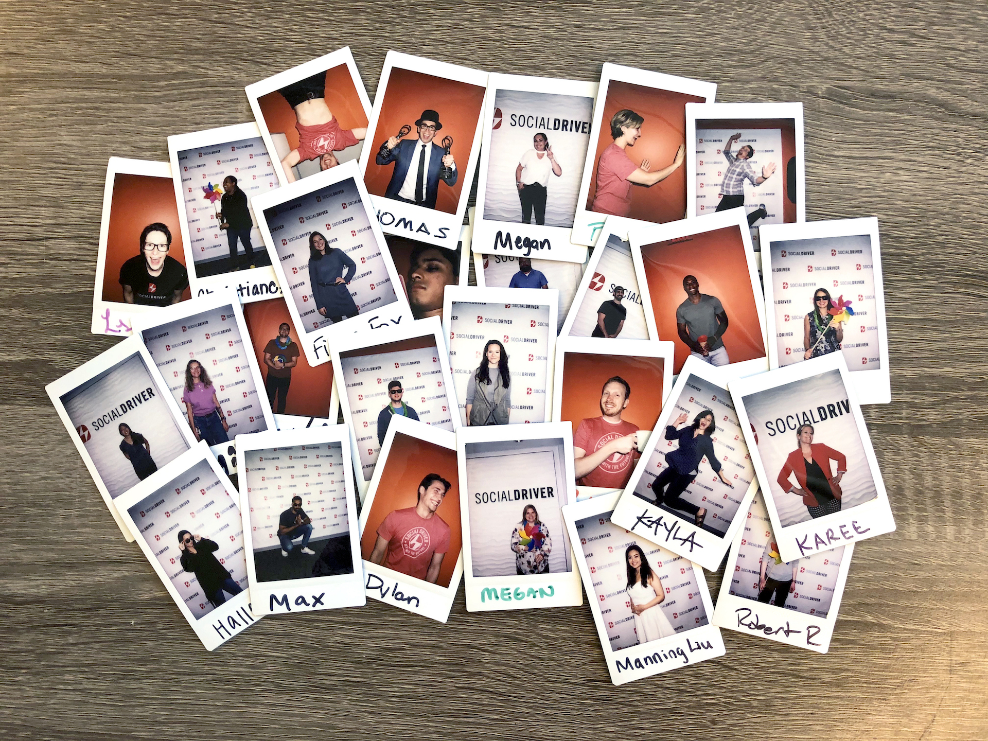A collection of Social Driver employee Polaroids arranged on a gray wood table.