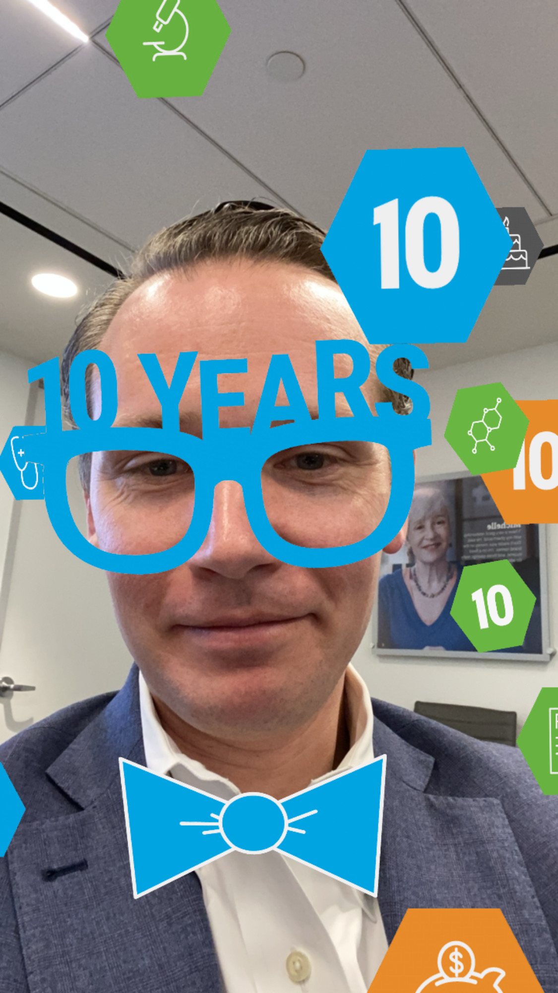 Man with brown hair and in a blue suit taking a selfie with Instagram lens that appears as bubble text and icons celebrating 10 of Biologics Price Competition and Innovation Act of 2010