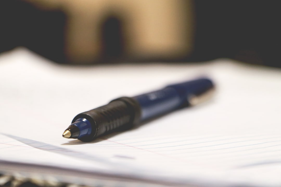 A pen lies on top of a stack of paper.