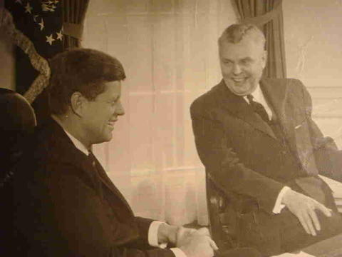 John F Kennedy .and John Diefenbaker sat at desk in the oval office.
