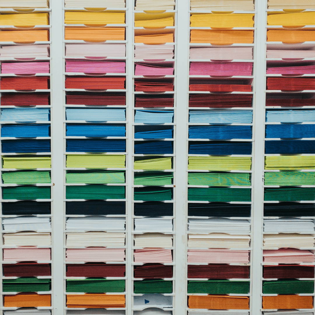 A stack of papers organized by color