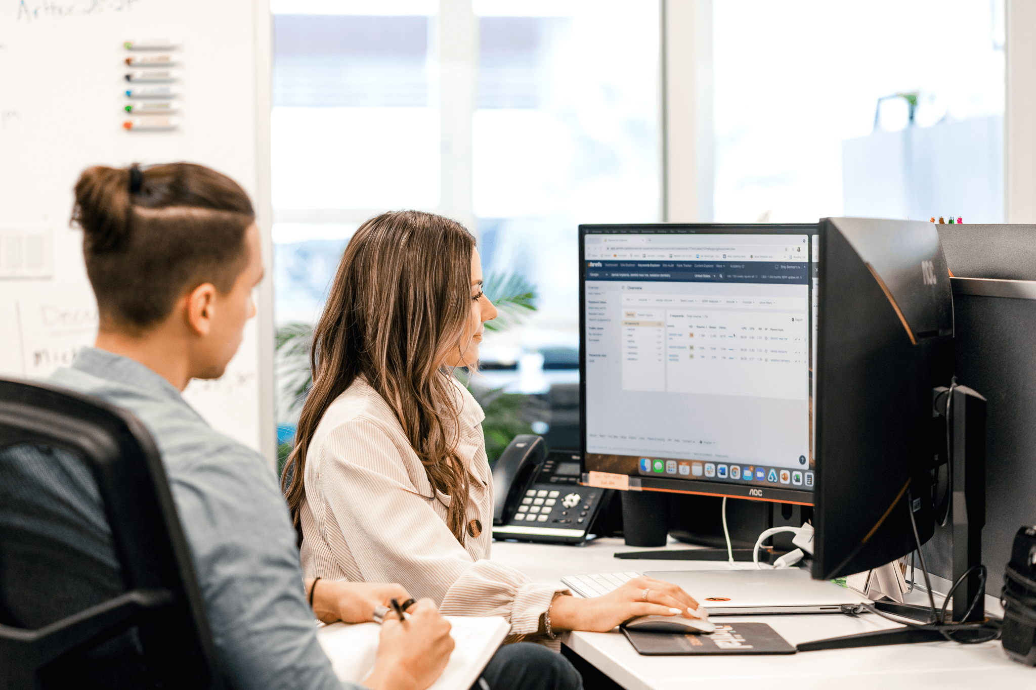 copywriter and account manager looking at keywords on computer