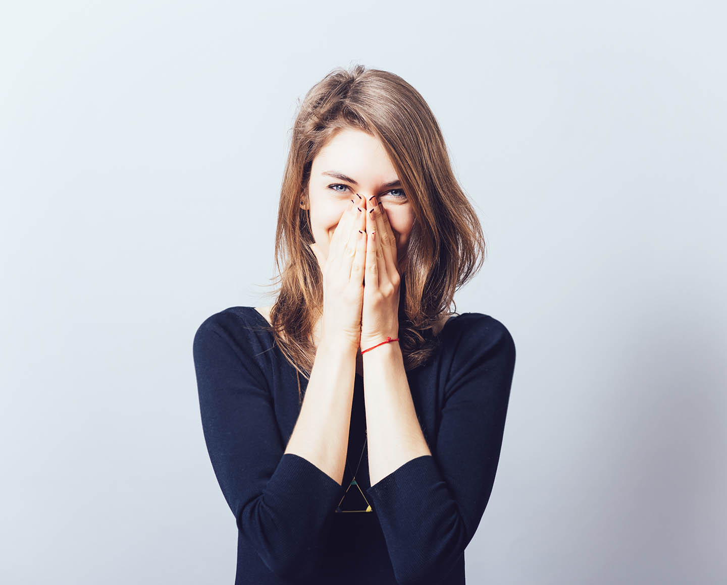 woman covering mouth smiling