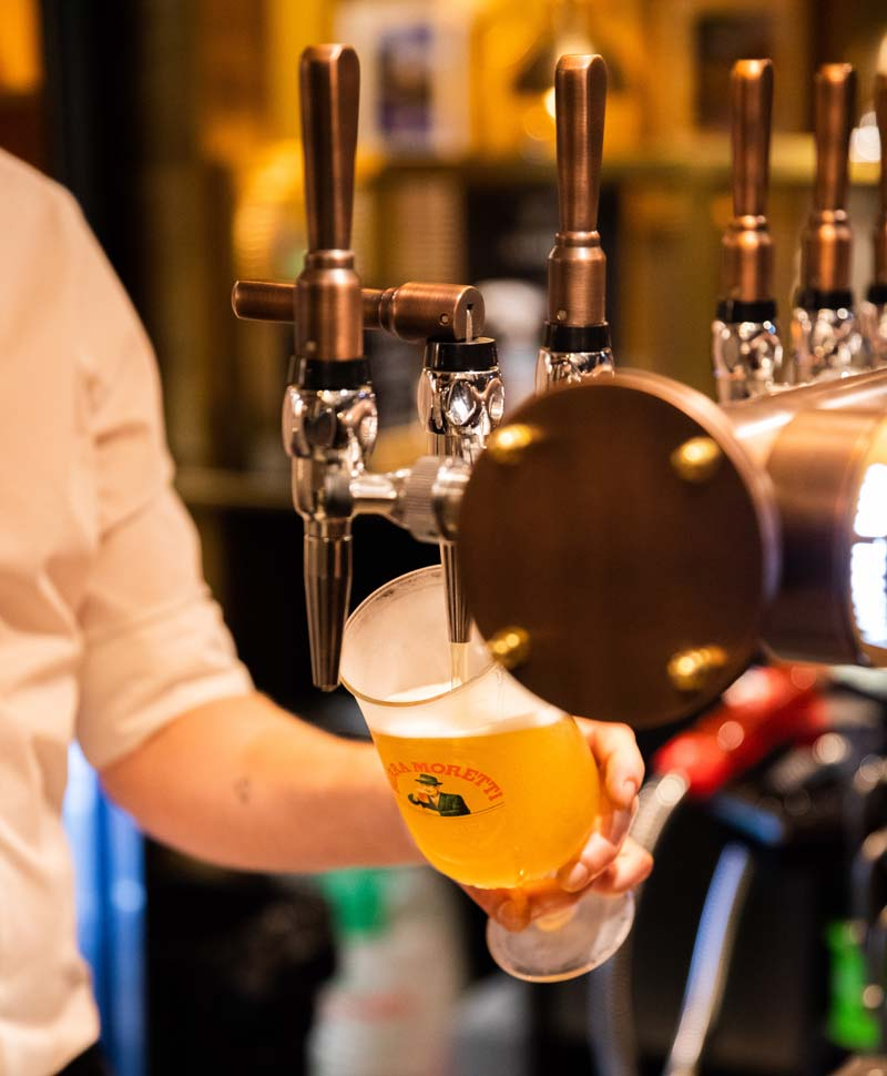 Pint of lager being pour from a tap in a pub