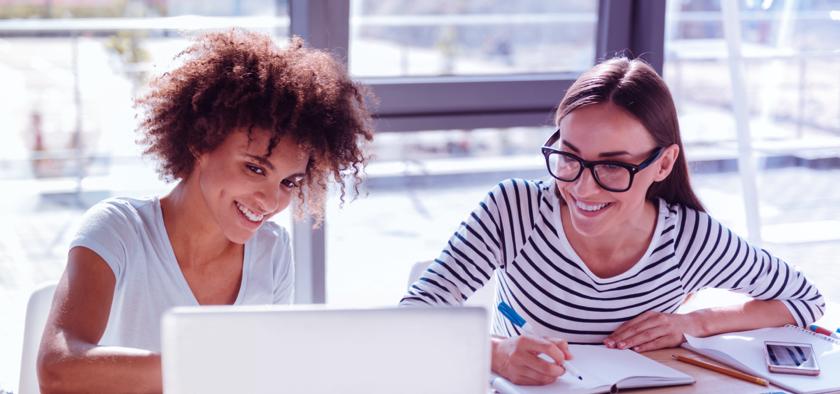 zwei junge frauen arbeiten zusammen an einem laptop