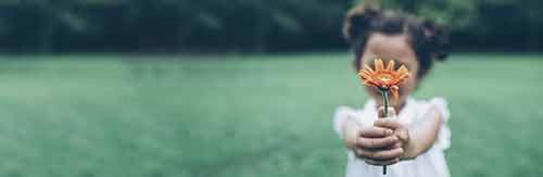 ein kind hält eine orangene blume hoch