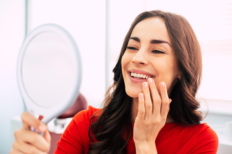 woman looking at teeth through mirror
