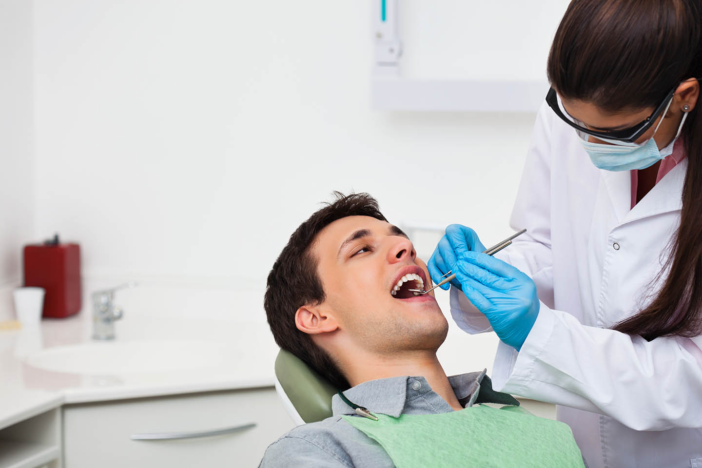 dental hygienist checking out a male patient's teeth