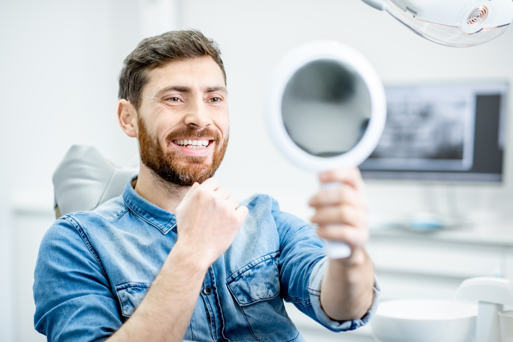 a man holding up a mirror smiling and looking at his reflection in dental chair