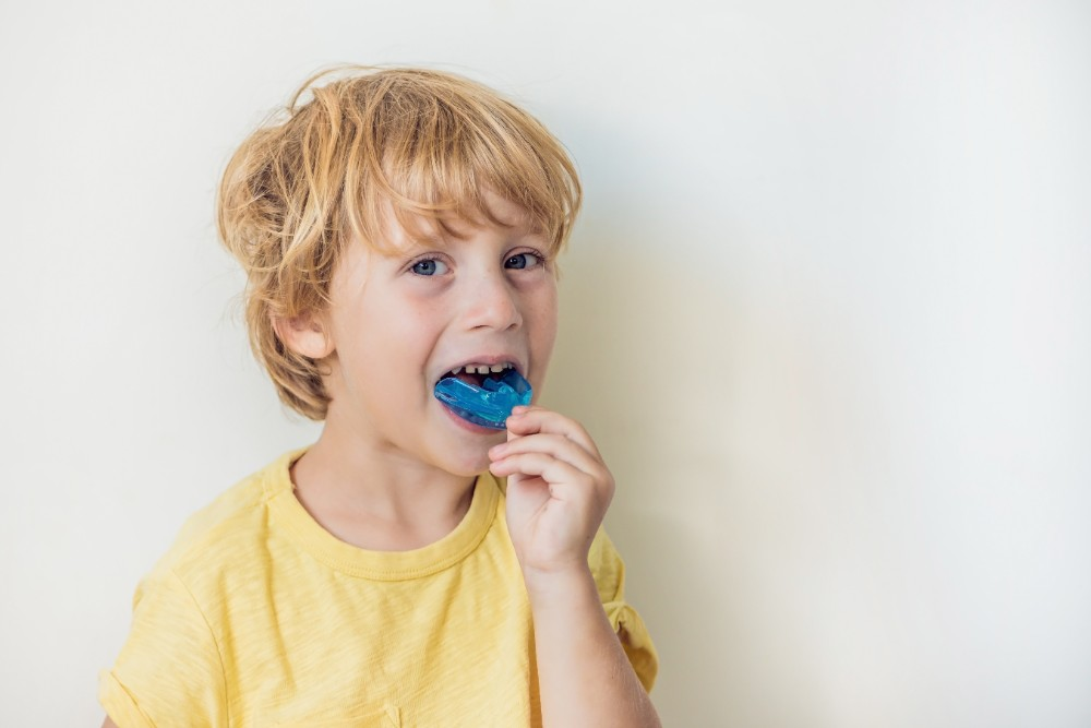 a child putting his myobrace in his mouth