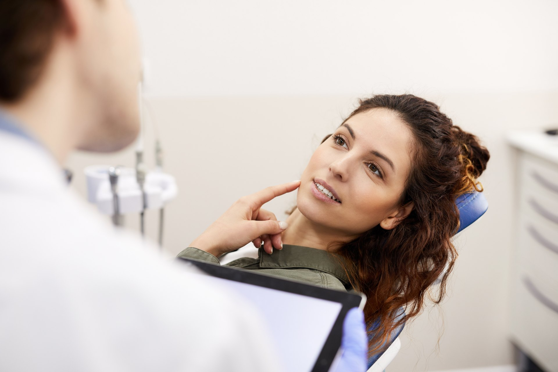 a woman patient pointing to the right side of her face as the dentist examines her