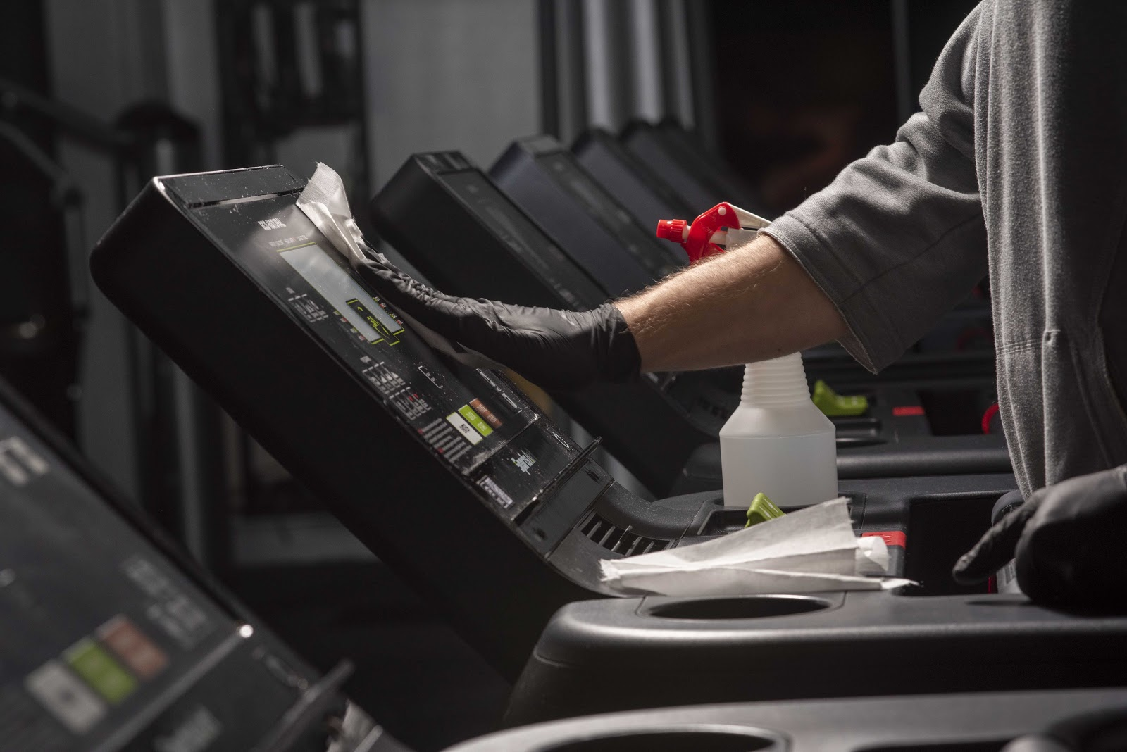 man wearing gloves disinfecting treadmill