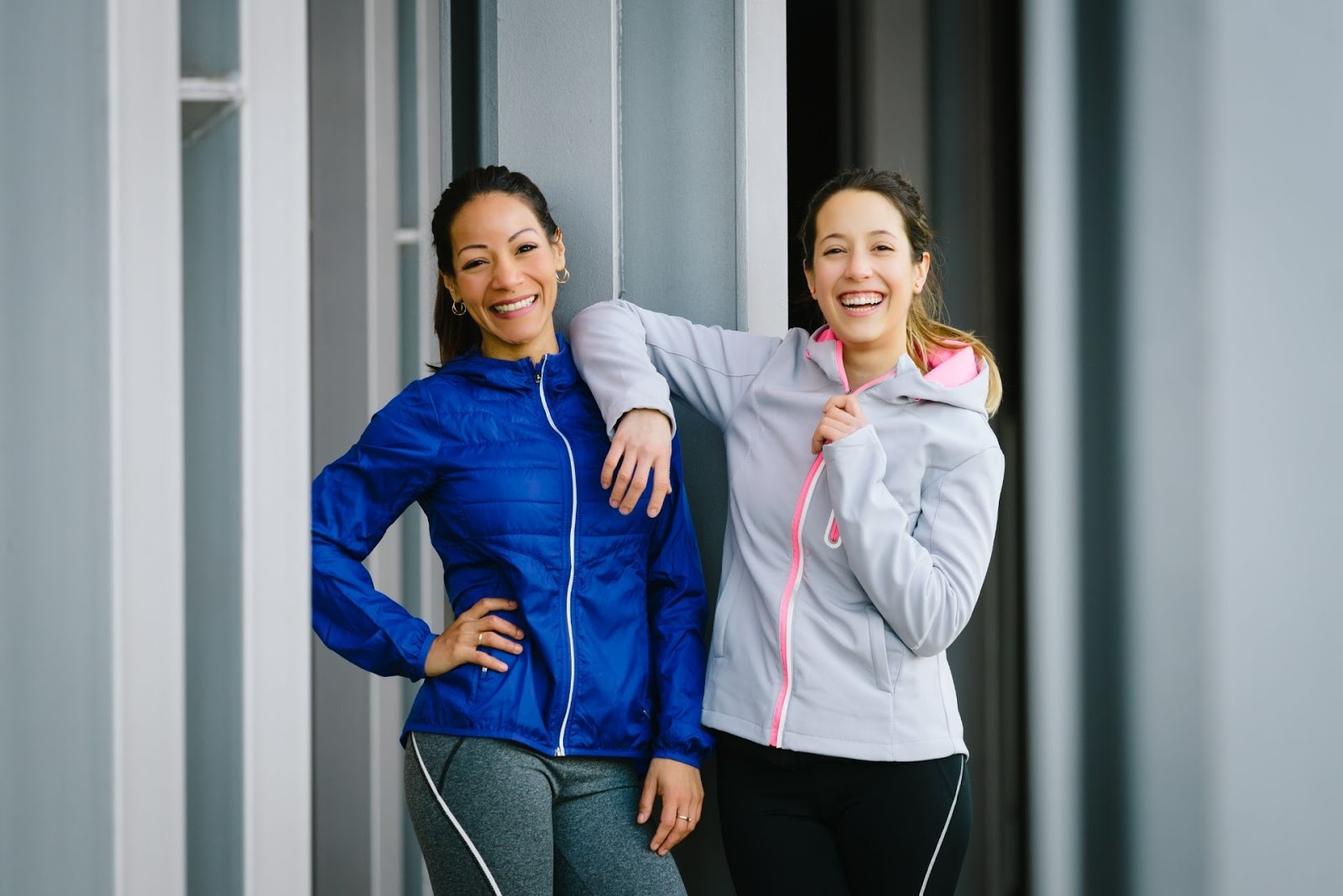 two woman standing outside in athletic outfits