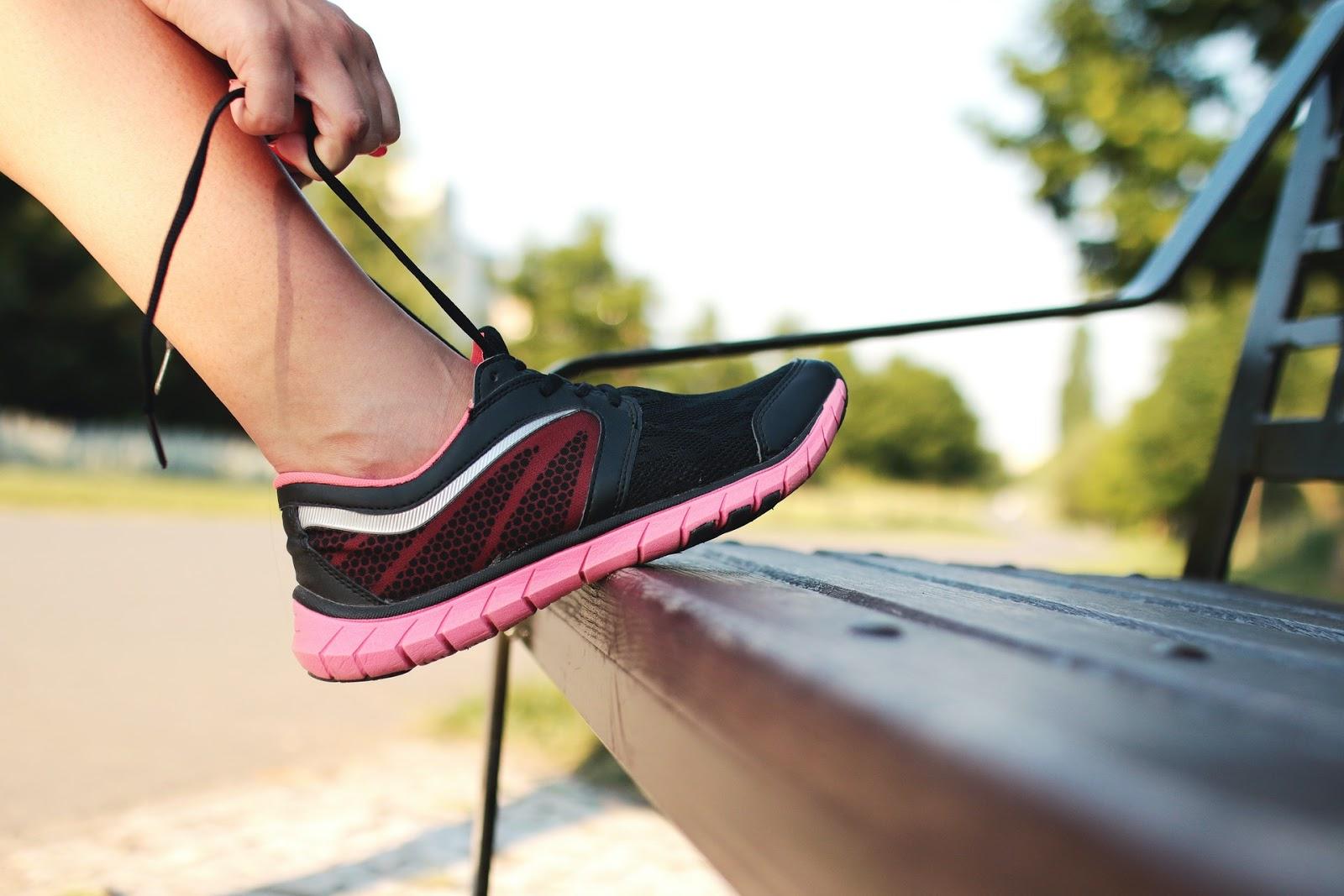 person tying running shoe