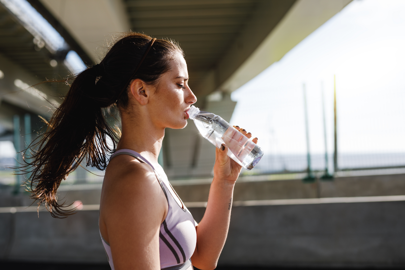 woman drinking out of water bottle