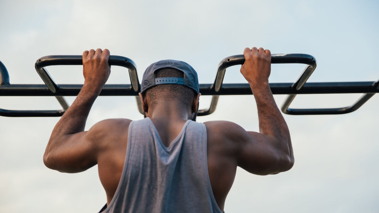 man pull up bar sky exercise arms tank top snapback hat