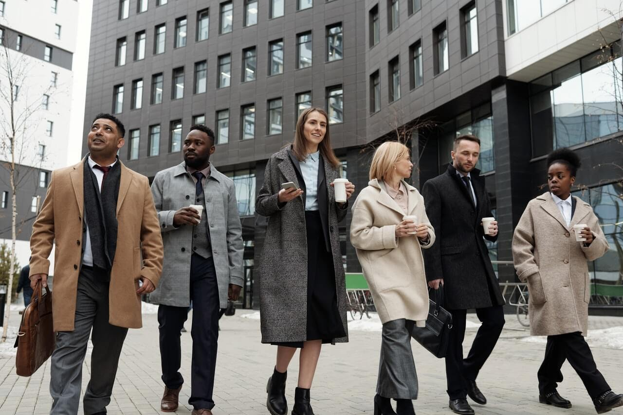 group of people coworkers waking coffee morning city gray building winter coats