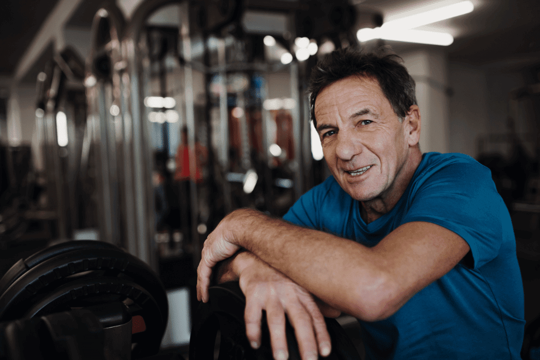 older man in gym looking at camera smiling accomplishment weight lifting machine