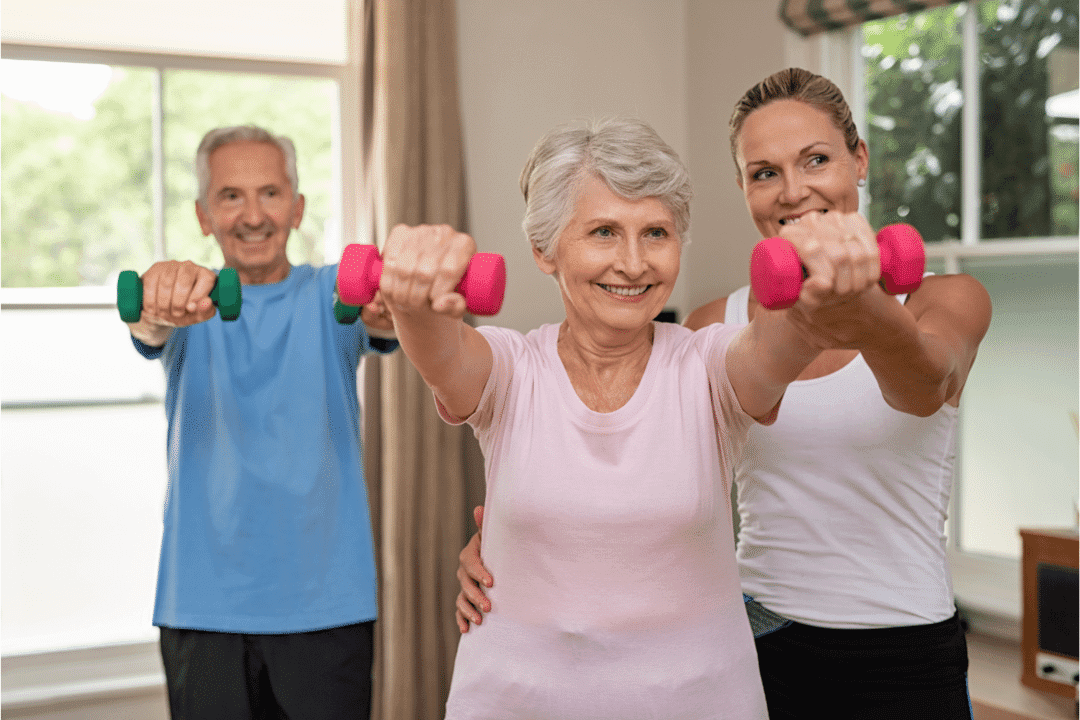 personal trainer helping older couple pink hand weights assistance smiling workout studio