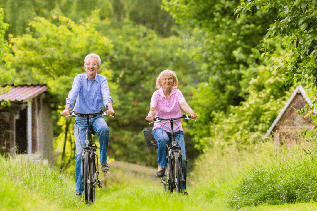 couple riding bikes through a field forest smiling wooden sheds summer green
