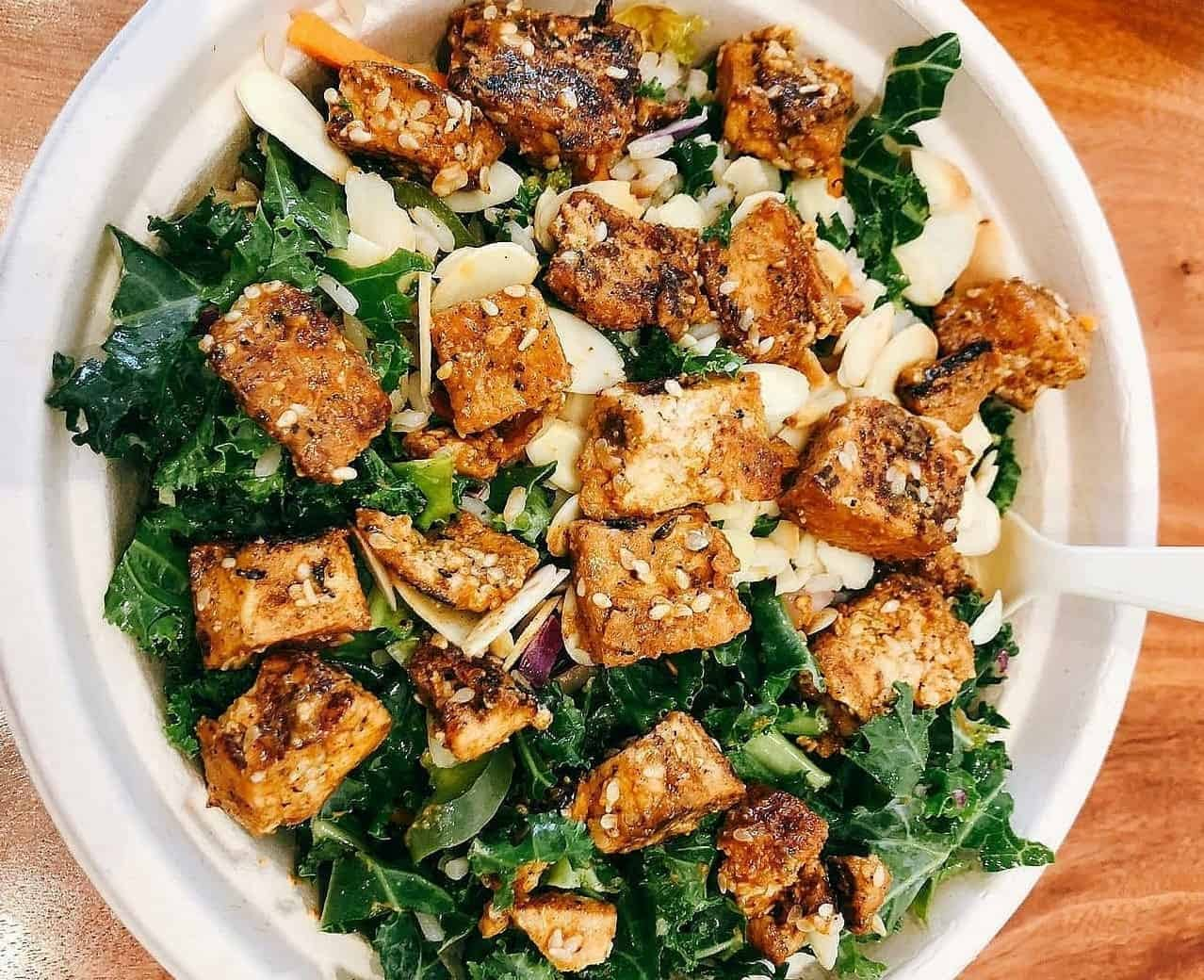 bowl of tofu and greens in paper bowl wooden counter kale sesame seeds