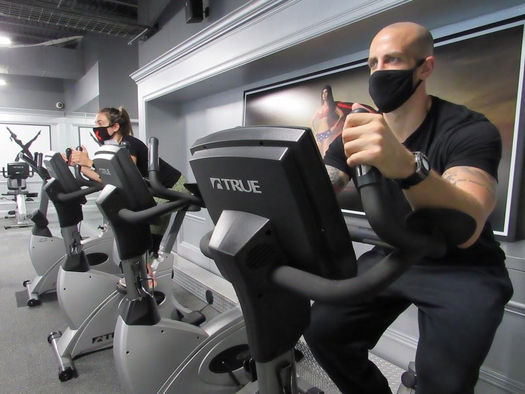 man and woman trainers on elliptical machine black sweats masks with x shadyside logo black gray room