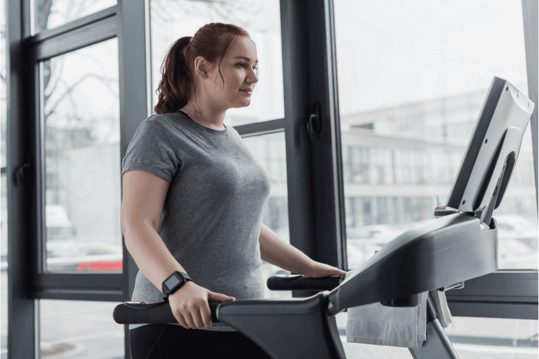 young woman on treadmill in gym next to large windows