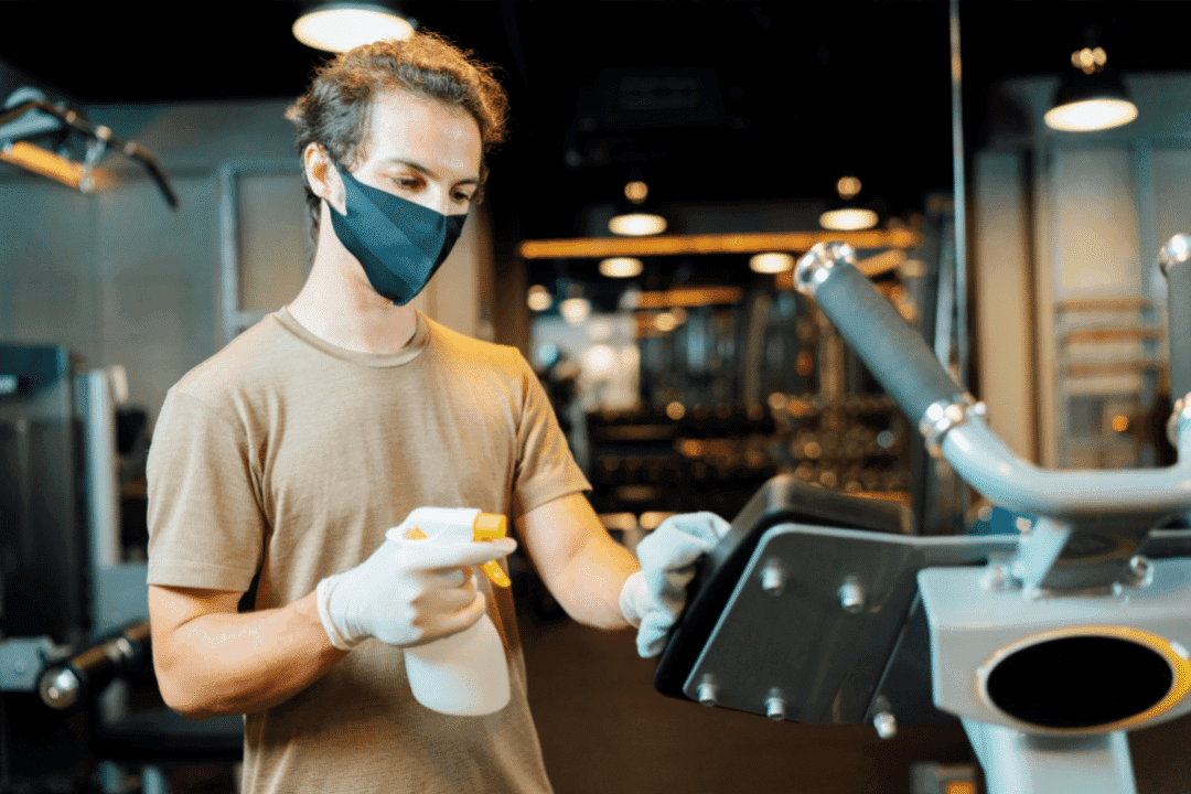 young man wearing mask sanitizing gym equipment with spray bottle