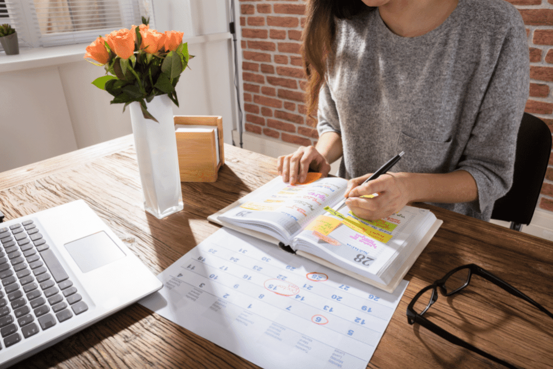 woman in sweater writing in planner on desk with flowers and computer