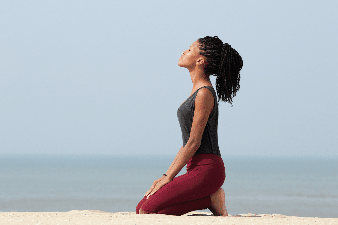 woman meditating on beach in workout clothes