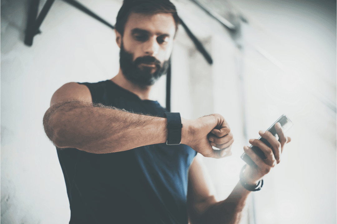 man checking watch fit bit pedometer during workout holding cell phone