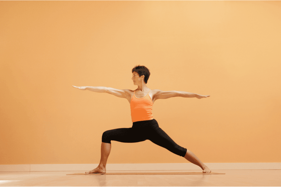 woman doing yoga in orange top in front of orange background