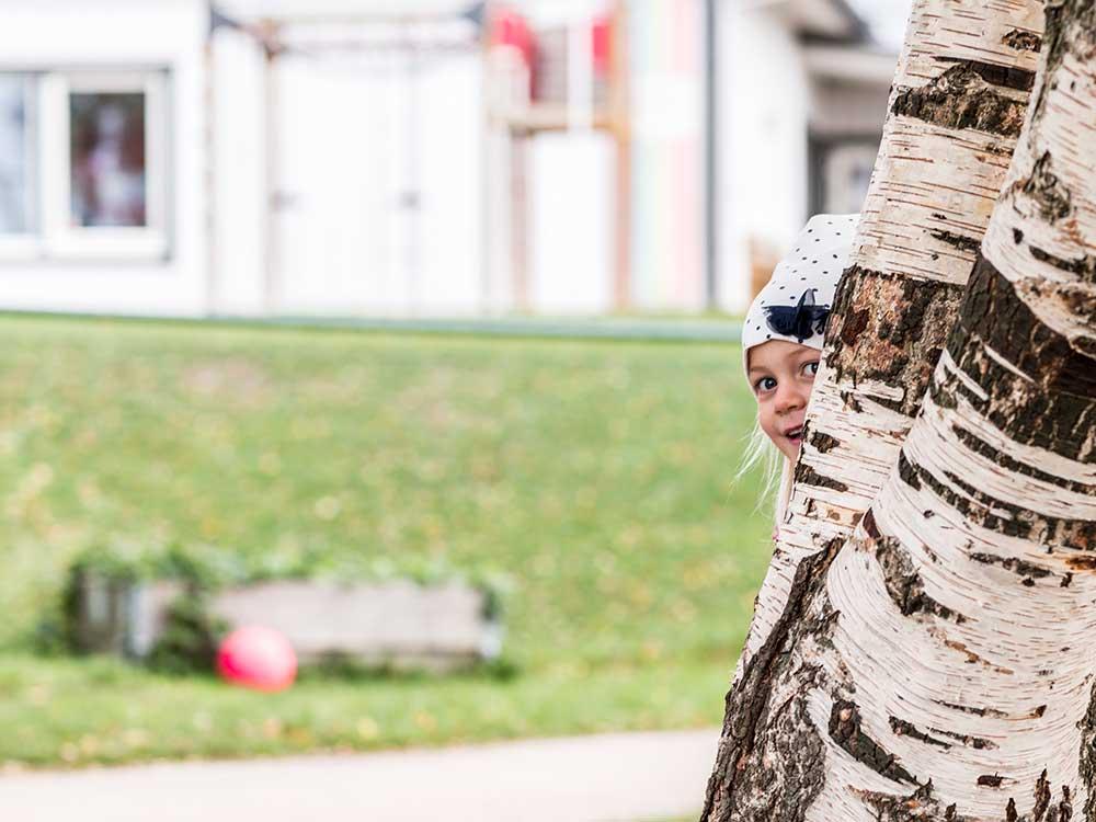 En tjej som leker kurragömma och gömmer sig bakom ett träd