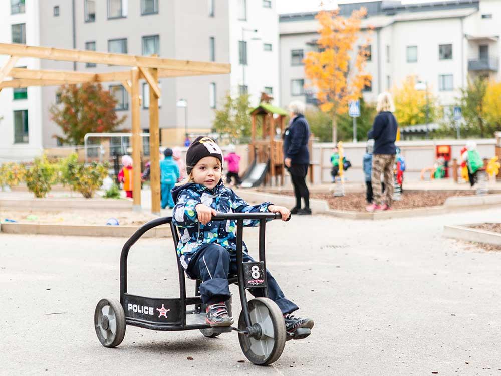 En tjej som cyklar utomhus på en trehjuling
