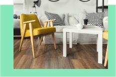Ein gelber Stuhl in einem Wohnzimmer auf Laminatboden