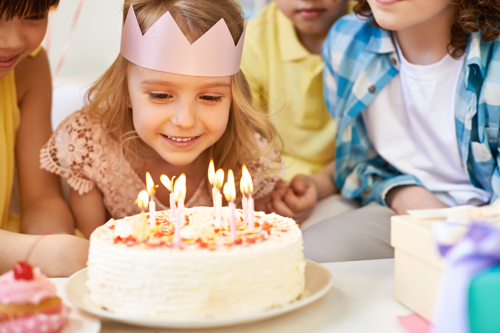 Young girl poised to blow out candles on birthday cake