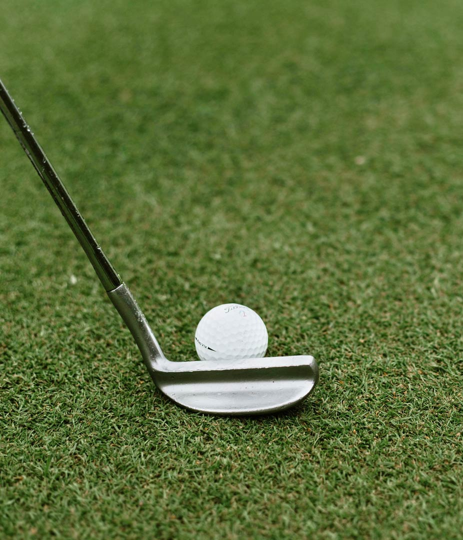 Close up of golf club at the ready. Photo by Will Porada on Unsplash