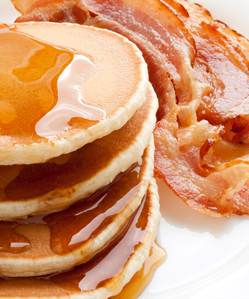 stack of pancakes with maple syrup and a side of bacon strips.