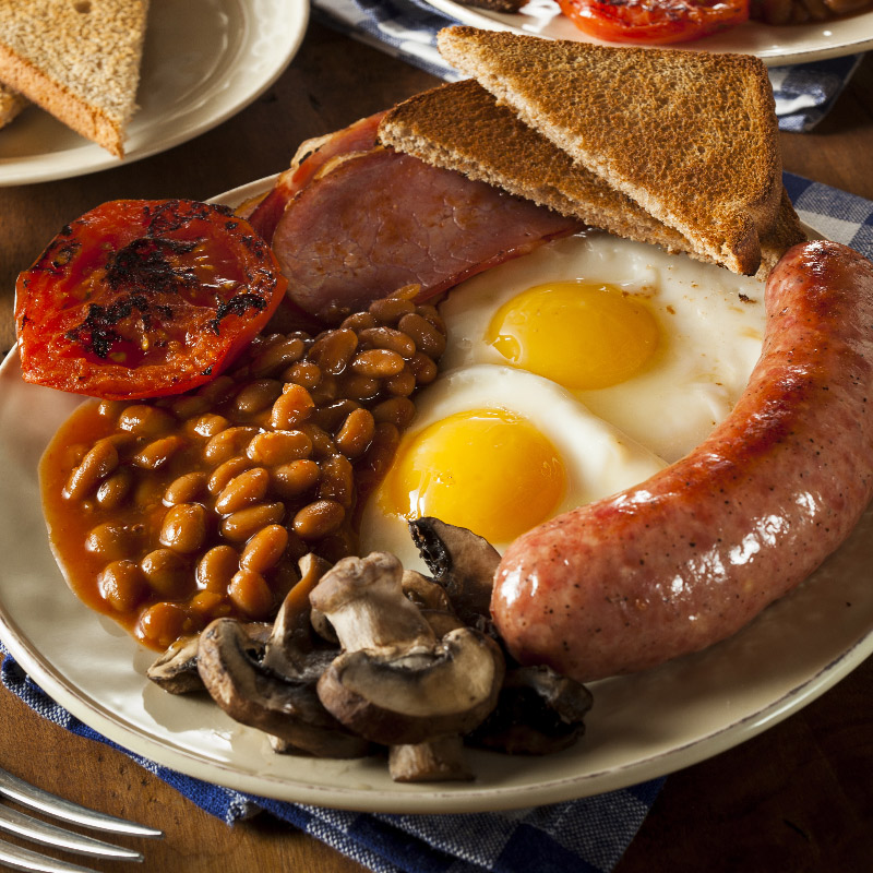 Breakfast spread of toast in a toast rack, fresh orange juice, croissant and a full English breakfast with bacon, beans, eggs, mushrooms, tomatoes and sausages.