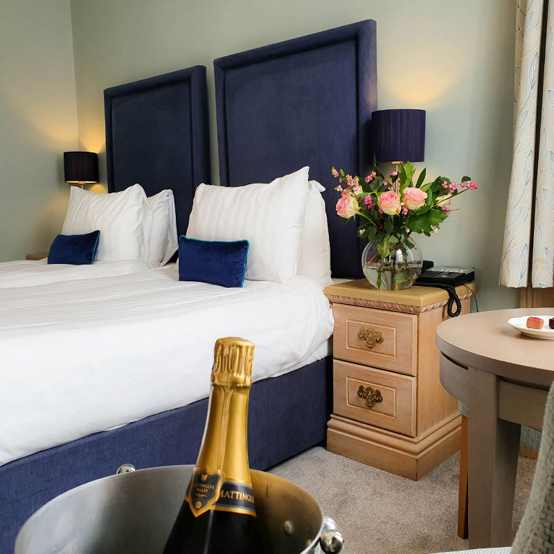 Twin beds in hotel bedroom with champagne bottle