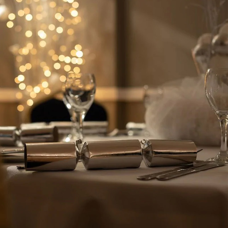 Dinner table decorated with lights and Christmas crackers for Christmas party