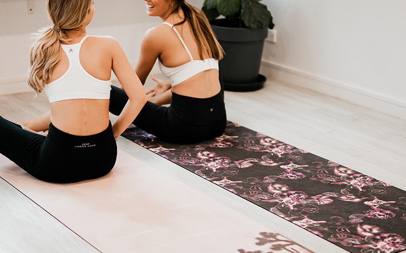 two women talking whilst sitting on yoga mats - photo by Luna Active Fitness on Unsplash