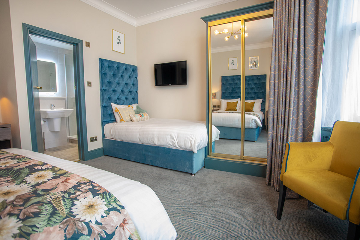 Bournemouth hotel double bedroom with bedside lamps and phone. decorated with two botanical paintings above the bed