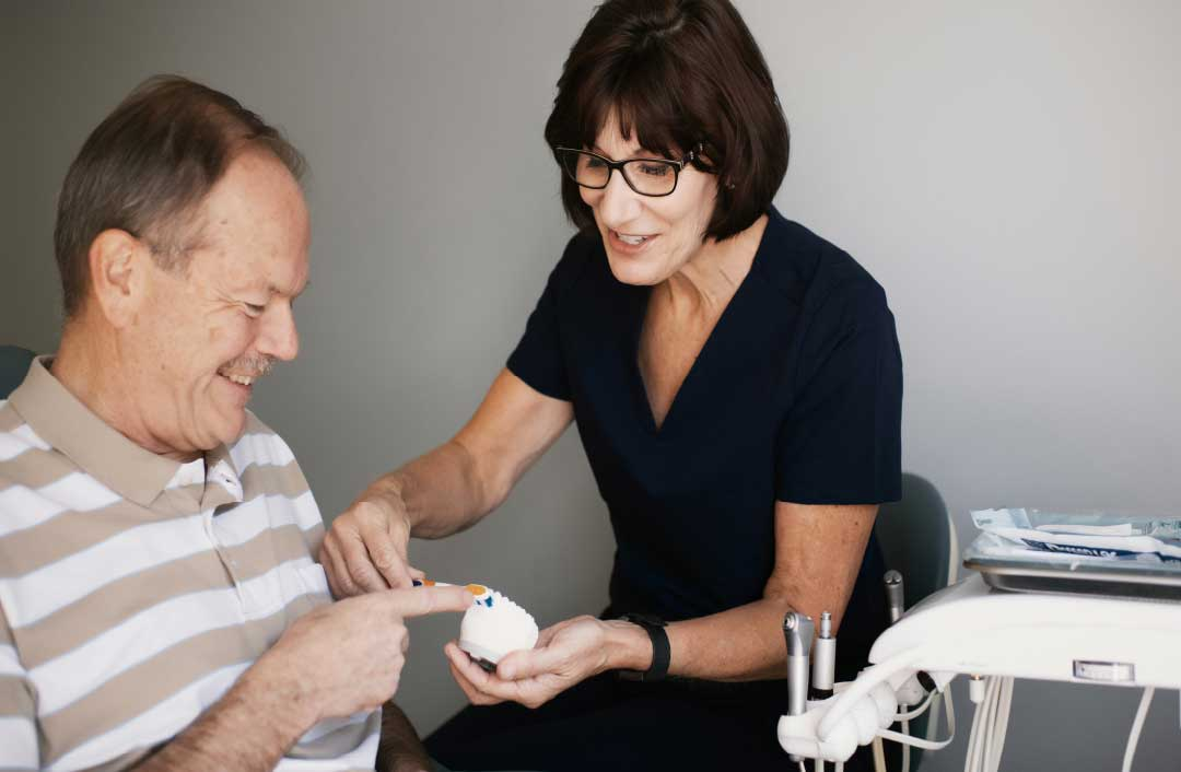 Photo of a team member and patient looking at a dental model