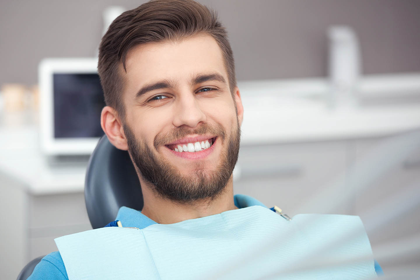 Man smiling while in dentist's examination chair