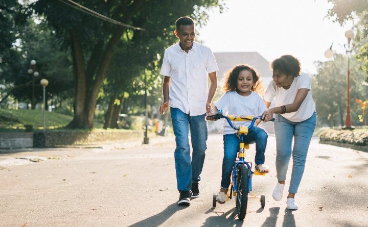 Two parents teaching their daughter to ride a bike